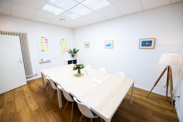 Unternehmungsberatung Oldenburg: Im Konferenzraum steht ein langer Tisch mit sechs Stühlen und einem Blumenstrauß. Der Raum ist hell und lichtdurchflutet.