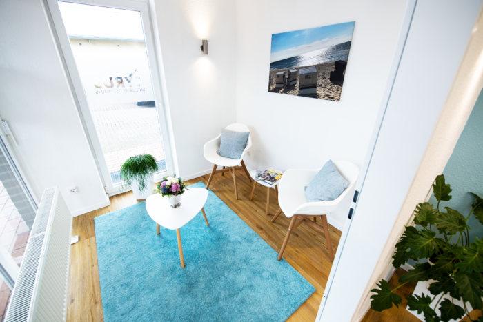 Unternehmungsberatung Oldenburg: Im Wartezimmer stehen zwei weiße Stühle und ein Tisch.