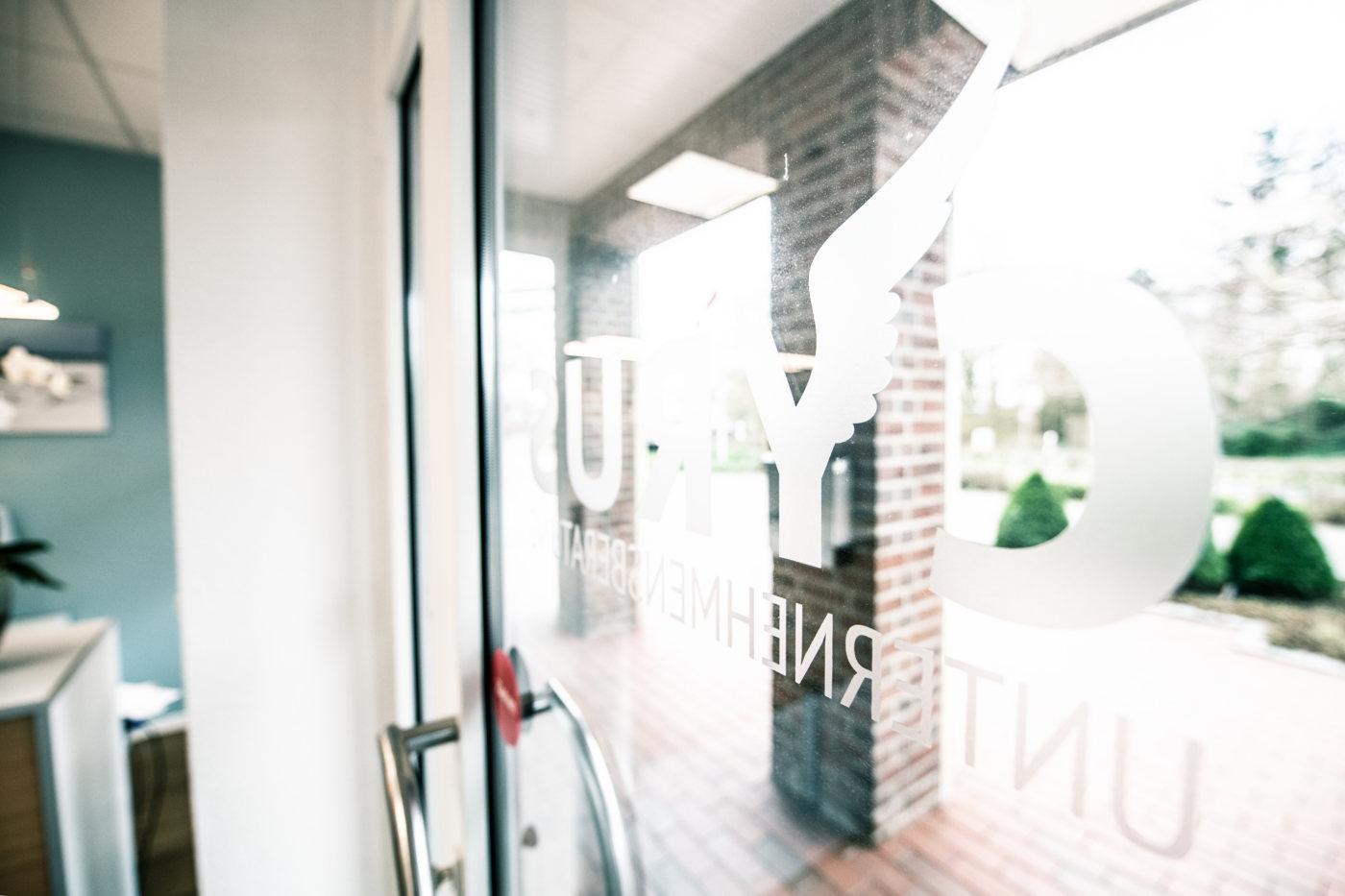 Unternehmungsberatung Oldenburg: Die Eingangstür aus Glas mit dem Cyrus Logo in weiß ist zu sehen.